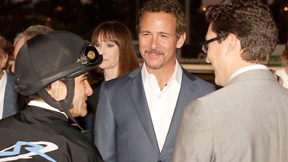 Co-owners Jim Rome, center, and Alex Solis II, right, enjoy Shared Belief 's victory with jockey Corey Nakatani after the Grade I $750,000 CashCall Futurity.